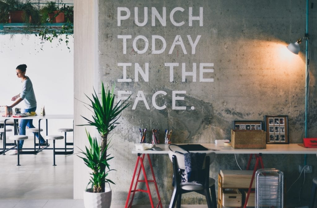 dizajnovy-priestor-na-pracu-napis-beton-ztena-stol-stolicka-rastlina-pomocky-na-pisanie