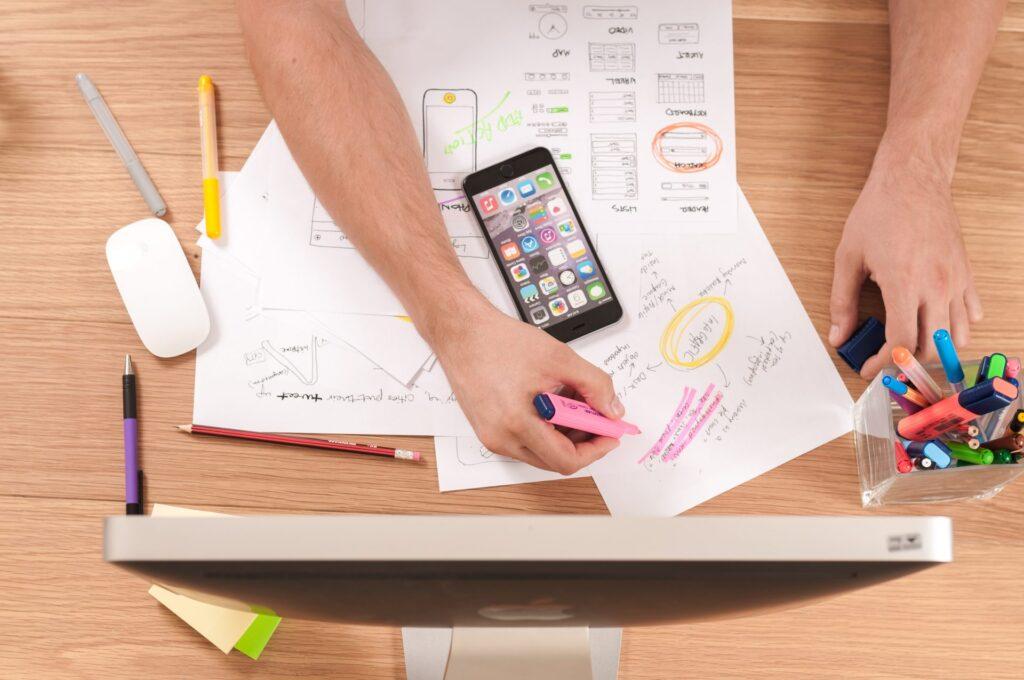 Stol-ruky-papiere-pera-fixky-telefon-planovanie-pocitac